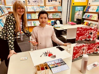 Fu Wenxheng and Mary Hare with illustrations created by Fu on the stand